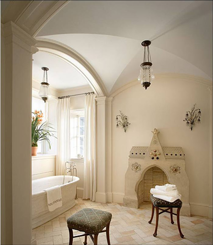 Bathroom by Katie Leede with barrel vaulted ceiling, stand alone tub, herringbone marble tile floor and a curved Moroccan style fireplace mantel