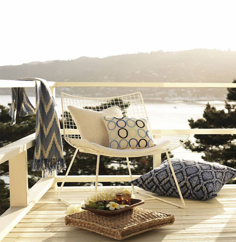 White wire outdoor chair sits on a deck overlooking the ocean by Sang An