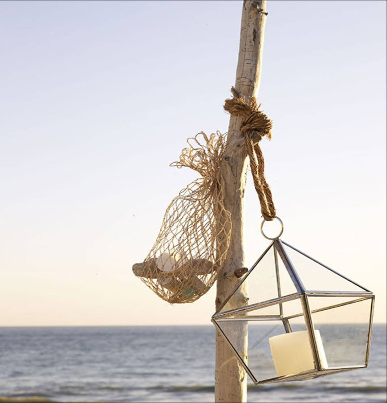 Reclaimed drift wood holds a glass lantern and a bag of small rocks on a deck overlooking the ocean by Sang An