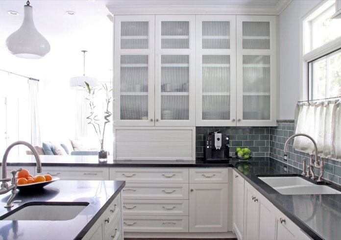 White kitchen with cabinets with recessed panel doors and drawers, reeded glass upper cabinets, slate subway tile backsplash, undermount sinks and dark stone countertops
