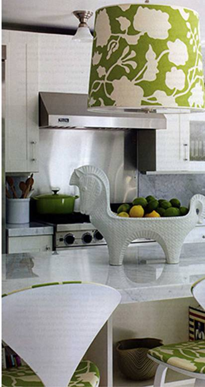 Modenr white kitchen by Jonathan Adler with a dome pendant light over an island made with a bold green and white printed fabric