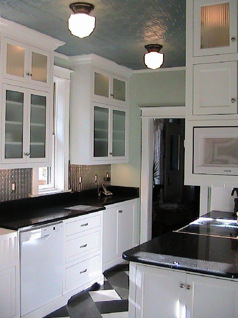 Kitchen after remodeling with plaid floor, white lower cabinets with recessed panels and glass upper cabinets and black quartz countertop