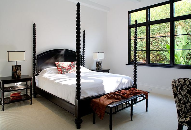 Bedroom in a Spanish revival home with black canopy bed, nightstand and bench and black paned windows
