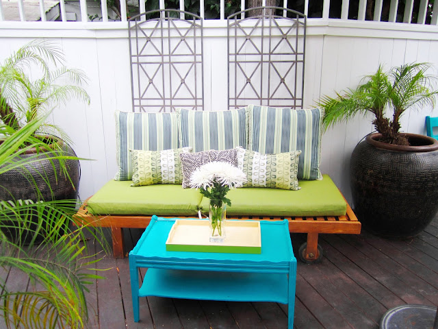 Brightly colored deck with a blue side table and playful accent pillows