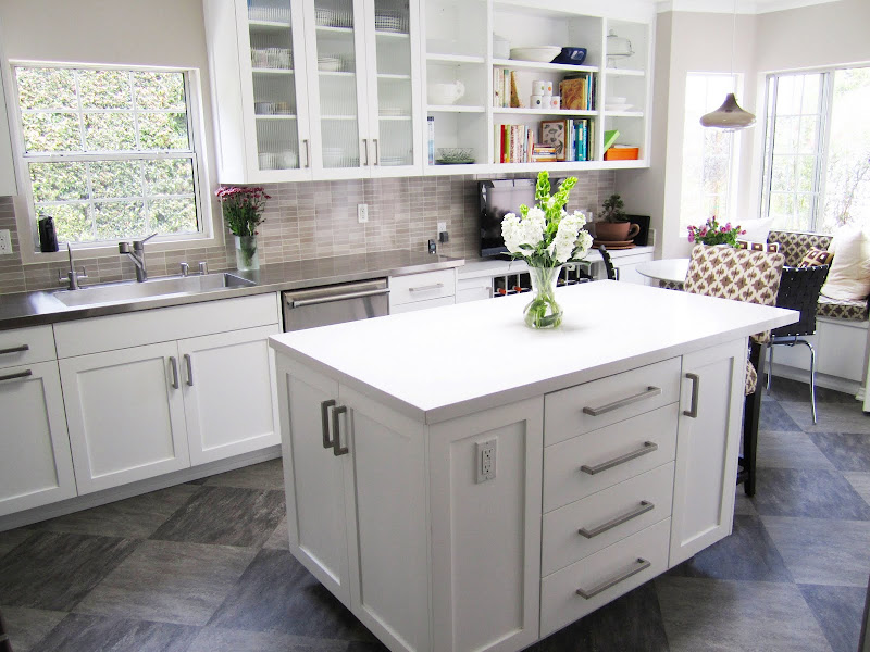 Gourmet kitchen with a breakfast nook, grey/brown backsplash, white paneled cabinets and hood and grey tiles arranged in a diamond pattern