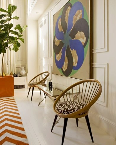 Dining room in Jonathan Adler's NYC home with two round chairs and decorative wall molding