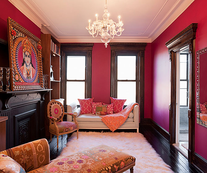 Fuchsia dressing room/lounge with a glass chandelier, custom cabinets and refinished wood floor