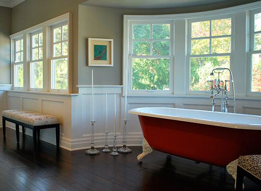Master bathroom with wood floor, half paneled walls, red claw foot tub and bay windows