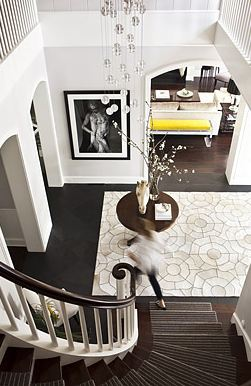 Foyer with a spiral staircase, dark wood floor, Kyle Bunting hide rug and a round table with a flower arrangement and horse head