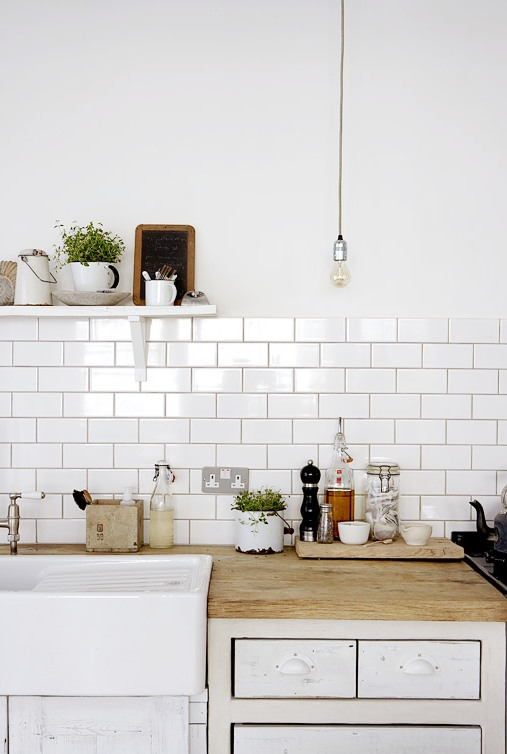 close up of the exposed bulb lighting white subway tile backsplash