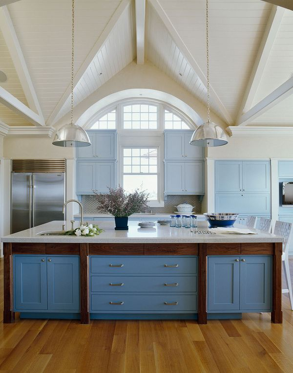 Kitchen with high vaulted ceilings, cornflower blue drawers and cabinets, wood floor, two nickle pendant lights,stainless appliances and an island with marble countertop