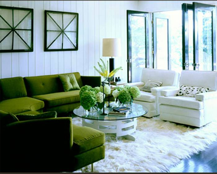living room with a green velvet sectional sofa white beadboard walls