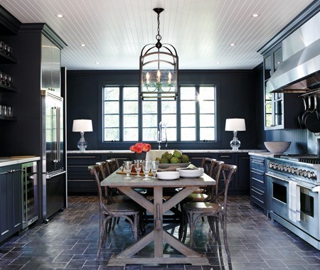 Eat in kitchen with dark cabinetry, cobellstons arraged like paver field tiles on the floor, white beadboard ceiling, a chandelier, a farmhouse table surrounded by matching chairs
