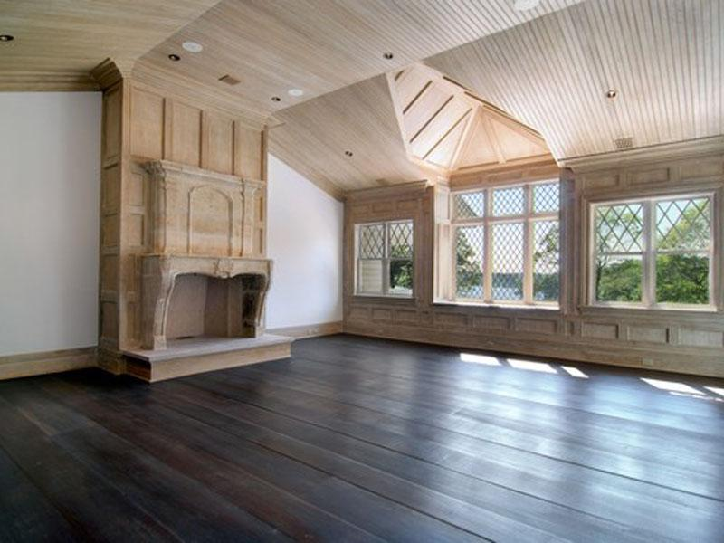 Master bedroom with light wood paneling and ceiling, wood floor and a fireplace
