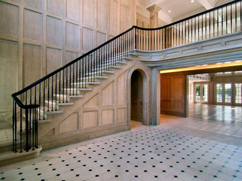 Foyer with French chalked wood paneling, black staircase railing and tile floor