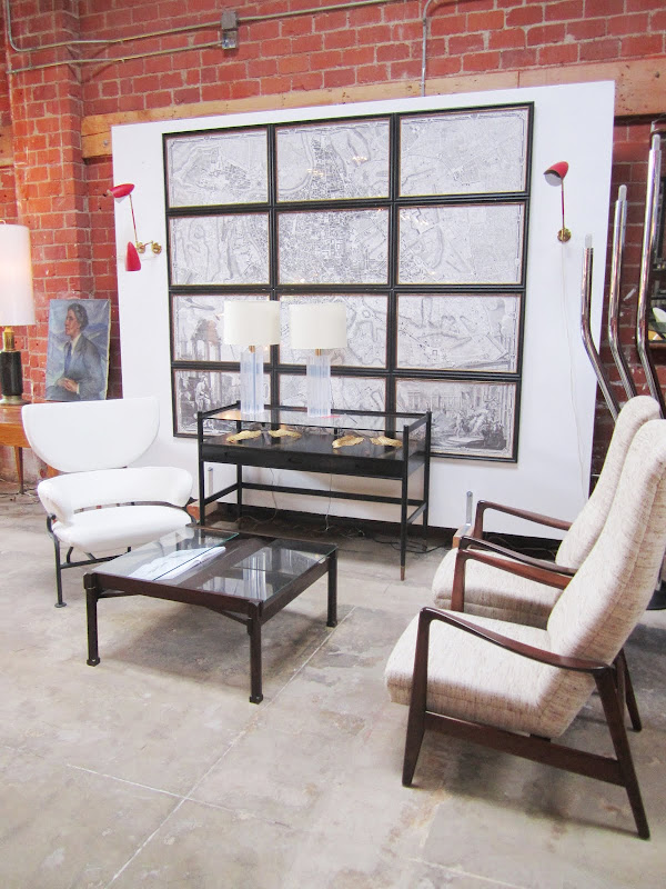 Room with brick wall with an Old map cut up and framed in sections behind a glass viewing table, three armchairs and a coffee table with a glass table top and iron legs