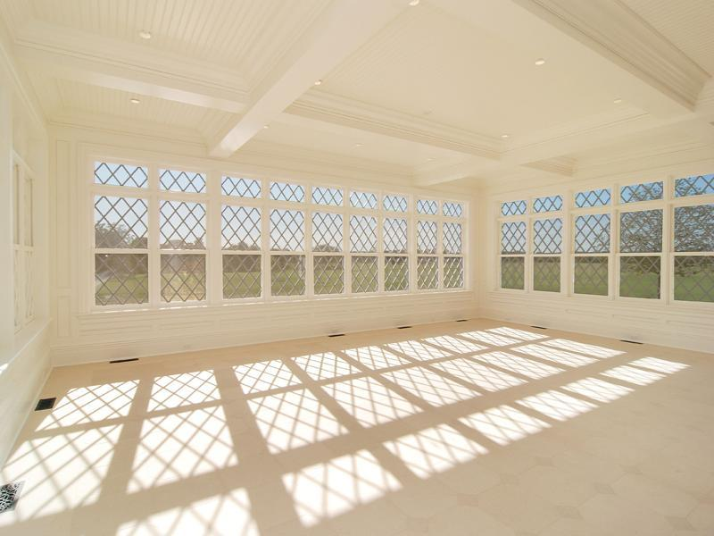 Possible sun room or dining room in an empty Hampton's farm with windows with a diamond pattern, a coffered ceiling and light tile floor