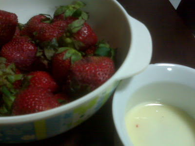 bowl of strawberries with cream on the side