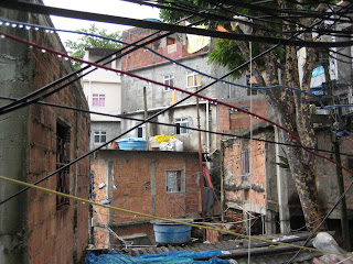Dripping electrical wires criss-crossing in front of the multi-storied structures within the favela.