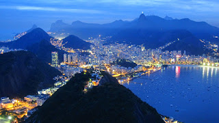 The city lights of Rio de Janeiro at twilight.  The lit statue of Jesus looks like a star above the city.