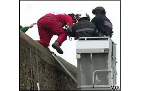 A Basque militant dressed like Santa Claus is taken away by a police officer after climbing on the wall of Sante prison