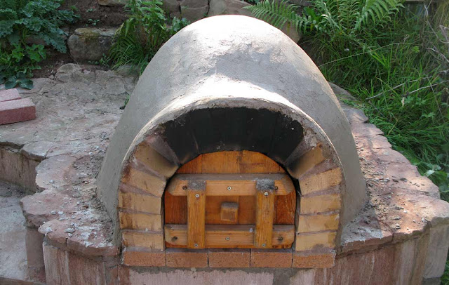 Front view of the earth oven with lime plaster finish and door.