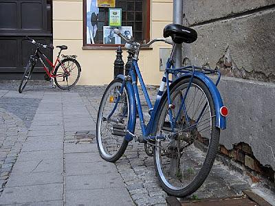 Stary rower przypięty do znaku drogowego