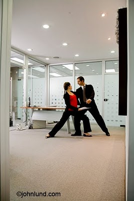 Tango dancers illustrate the concept of teamwork and negotiation in a business office setting