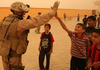 A U.S. Marine gives an Iraqi child a high-five during a patrol through Fallujah.