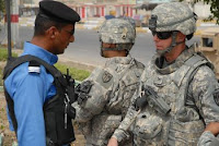 Col. Mark Spindler (right), commander, 18th Military Police Brigade, discusses operations with an Iraqi policeman at a checkpoint, July 31. Army Maj. Gen. Mark P. Hertling, commander of Multinational Division North, said Iraqi Security Forces have contributed to a sharp decline in violence.