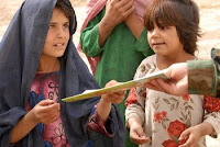 A young Afghan girl receives an educational book from an Afghan Commando during a humanitarian assistance mission in the Mandi Sar village, Kandahar province Sept. 8.