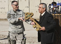 Lt. Col. Michael Pappal hands the 'key' to FOB Callahan over to Anys Faleyeh, general manager of the Ministry of Trade, at the Sha'ab Market, Jan. 3. The ceremony symbolized Iraq's increasing sovereignty in the Adhamiyah District of Baghdad.
