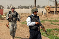 Spc. Dane Bamford (left), from Shamokin, Pa., searches with an Iraqi policeman during a joint operation at Baghdad University College of Agriculture March 21. As Iraqi Security Forces step into a larger role, U.S. troops will step back, allowing for less stress on forces and more 'home time' for troops.