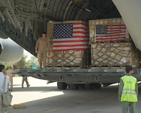Airmen unload crates of humanitarian aid upon arrival in Islamabad, Pakistan Wednesday. The aid items are bound for displaced Pakistanis in the North West Frontier province.