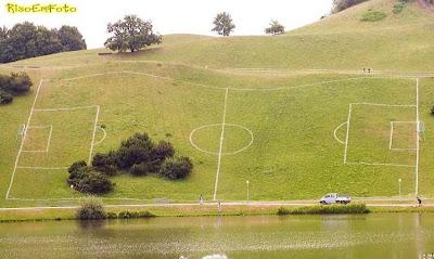 Campo de futebol demarcado em uma encosta de morro íngreme.