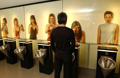 banheiro masculino com fotos de mulheres olhando para quem esta fazendo xixi