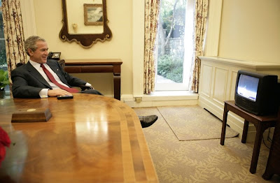 Bush sorridente, na casa branca assistindo televisão, como se tudo estivesse muito bem. Puro relax!