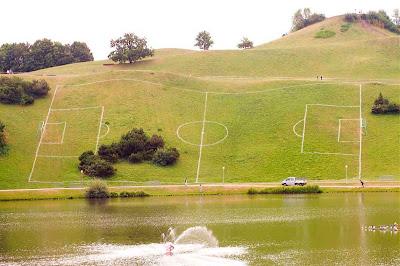 Campo de futebol demarcado em uma colina torta e com árvores no meio.