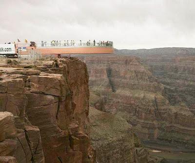 Vista lateral mostra turistas sobre o abismo.