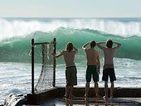 Surfistas observam as condições das ondas.