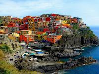 Foto de povoado com casas muitas coloridas em pequena montanha à margem do Mediterrâneo.