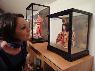 Fotografia de Cristina Silva a observar uma boneca japonesa