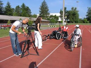 A equipa do Consigo na pista de atletismo de Genève, com dois entrevistados do Club en Fauteil Roulant