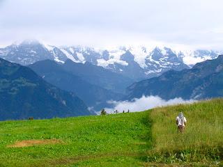 Paisagem de montanha, na Suíça, com Manuel Loureiro, operador de câmara, de costas a fazer imagens
