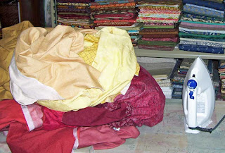 A big pile of pre-washed fabric awaiting ironing.