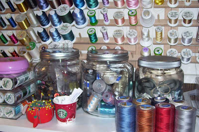 Three glass jars hold an assortment of sewing supplies for future projects.