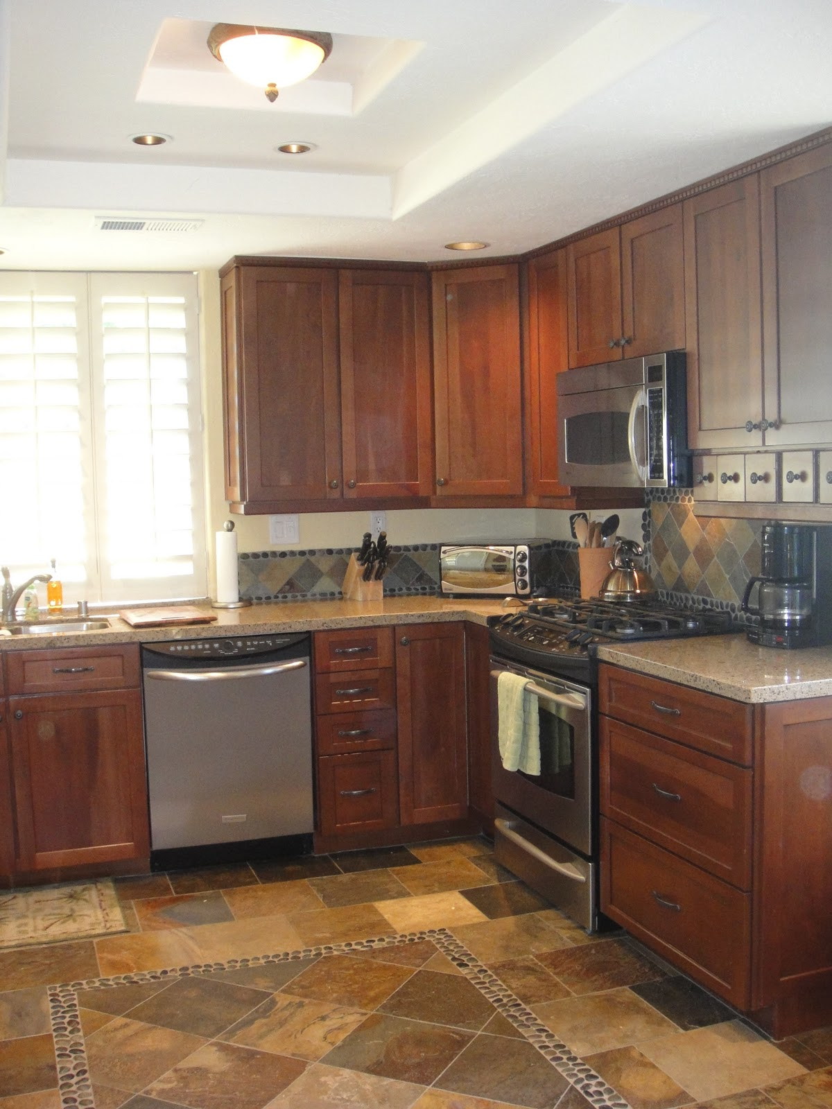 Kitchen with dark walnut stained cherry wood cabinets, granite