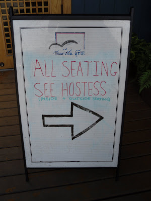 Sandwich board: Please see hostess for indoor / outdoor seating. (Marina Side Grill, North Vancouver, BC)