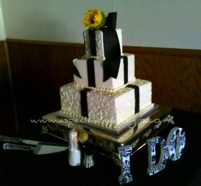 A lovely black and white cake accented with a yellow sunflower