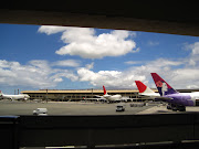 This is a picture through a part in the airport of the pretty airplanes. (img )